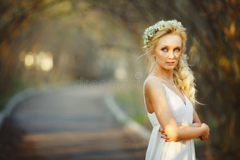 白色礼服和花卉花圈的美丽的白肤金发的妇女在她的头 胡同的逗人喜爱的人 免版税库存照片