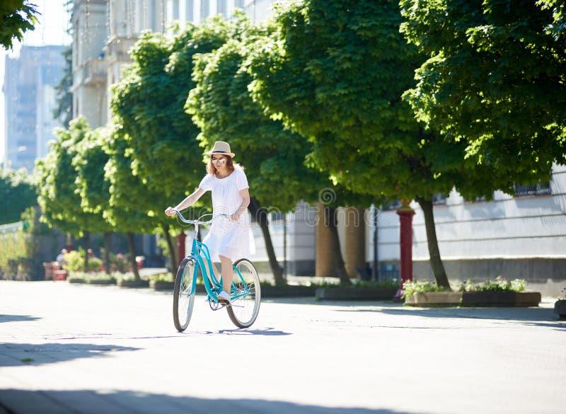 白色礼服和草帽的年轻女性在被铺的市中心的骑蓝色自行车 库存图片