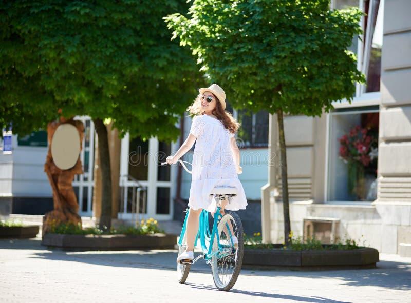 白色礼服和草帽的微笑的女性在被铺的市中心时看回到照相机,当骑蓝色自行车 免版税库存照片