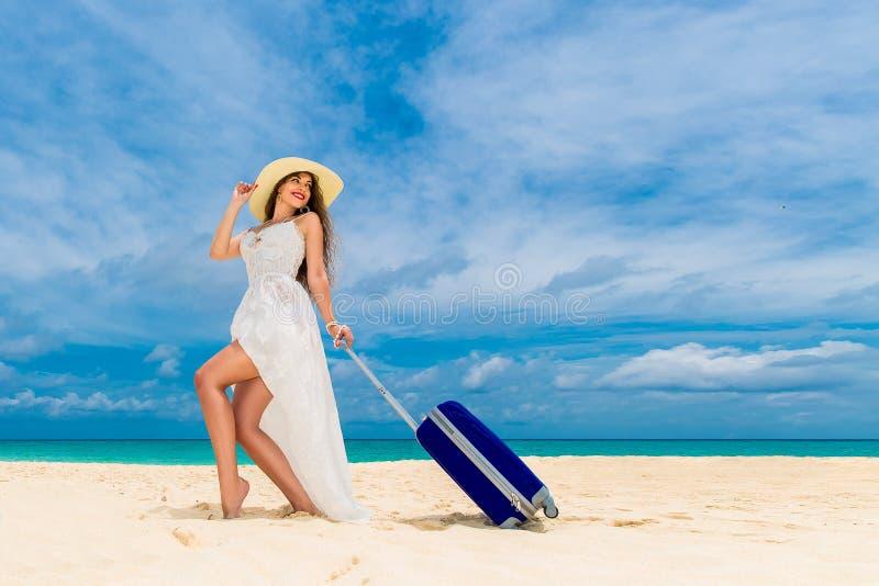 白色礼服和草帽的美丽的少妇有suitca的 免版税库存照片