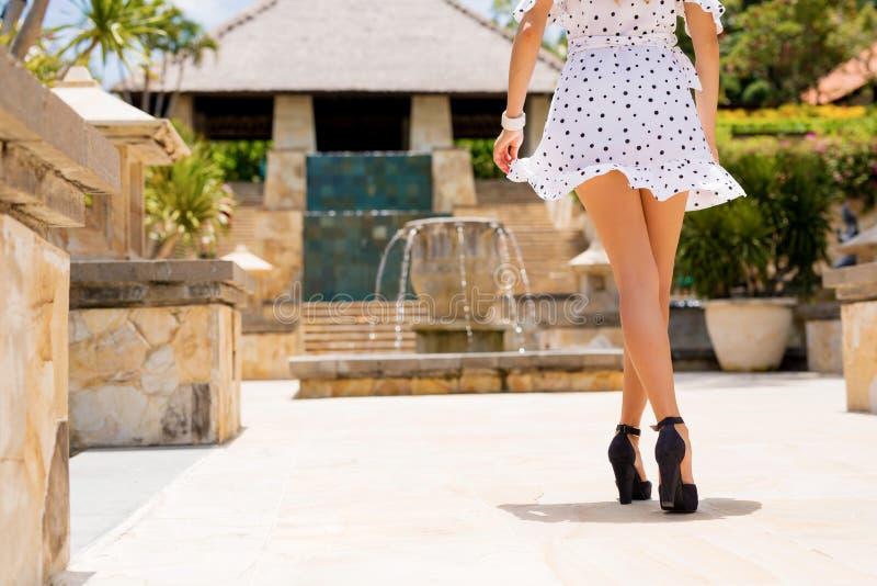 白色礼服和黑脚跟的妇女 免版税库存照片