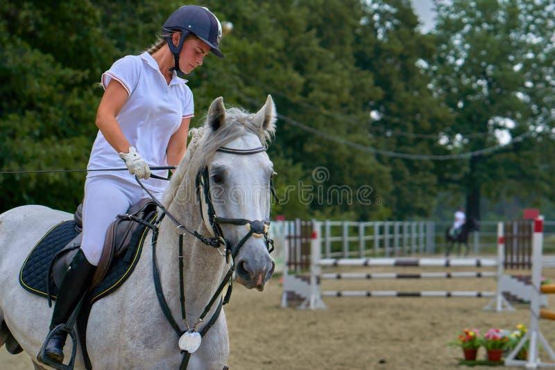 白色礼服和黑起动的少妇骑师,在骑马竞争参与 免版税库存照片