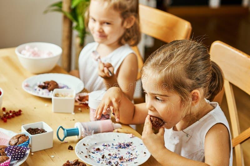 白色礼服的两个美丽的姐妹装饰并且吃可口杯形蛋糕 免版税库存照片