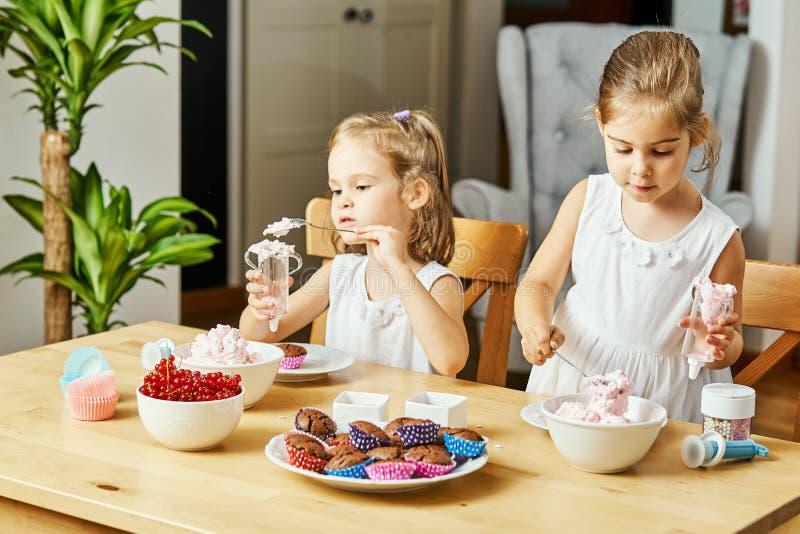 白色礼服的两个美丽的姐妹装饰并且吃可口杯形蛋糕 图库摄影