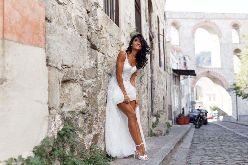 白色礼服的华美的新娘在希腊市附近,显示他的腿,姿势在白色石墙附近在街道在夏时 库存图片