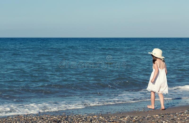白色礼服的单独走的小女孩海,使用在海滨 免版税库存图片