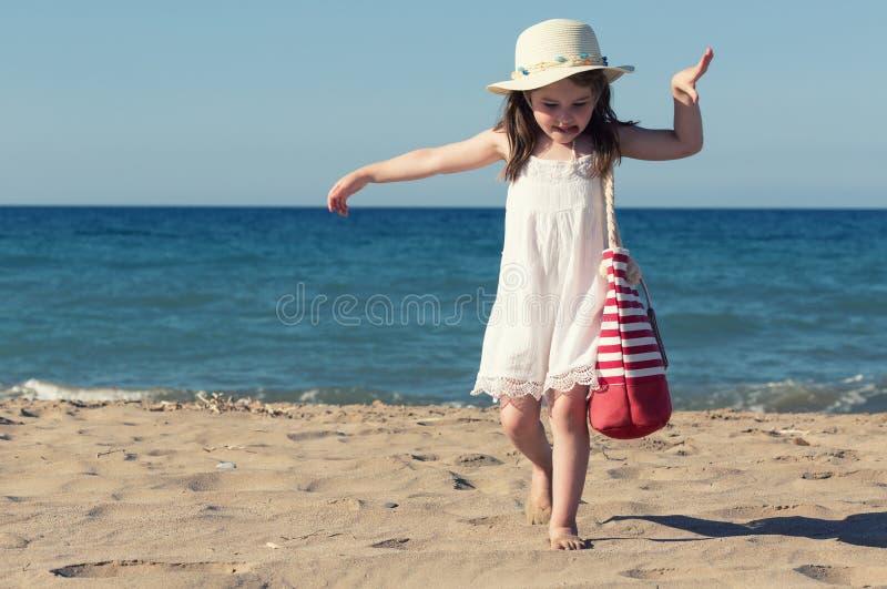 白色礼服的单独走的小女孩海 图库摄影