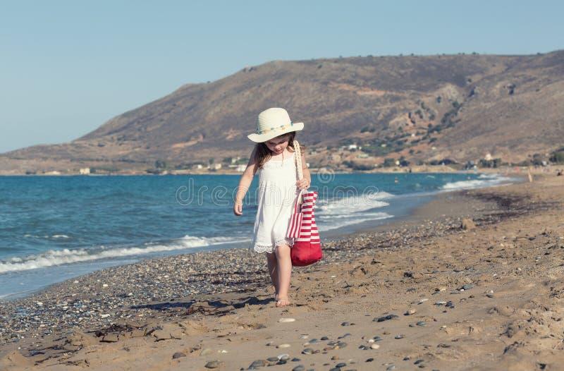 白色礼服的单独走的小女孩海 免版税库存图片