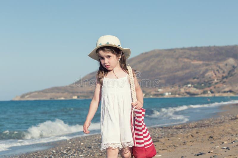 白色礼服的单独走的小女孩海 免版税库存照片