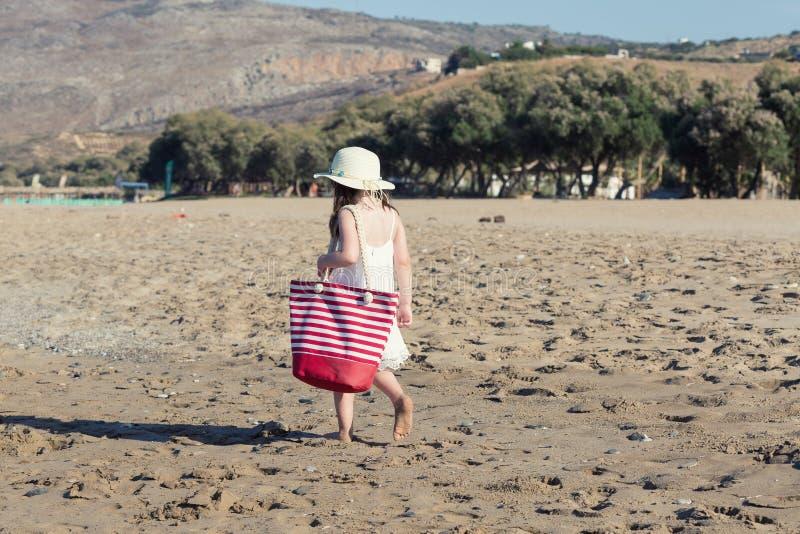 白色礼服的单独走的小女孩海 库存照片