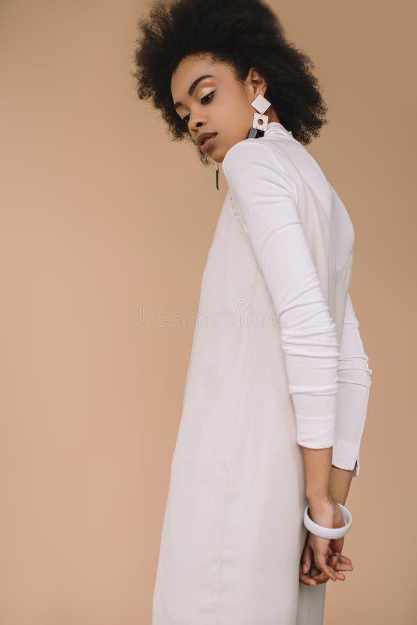 白色礼服的可爱的年轻女人有耳环的 免版税库存照片