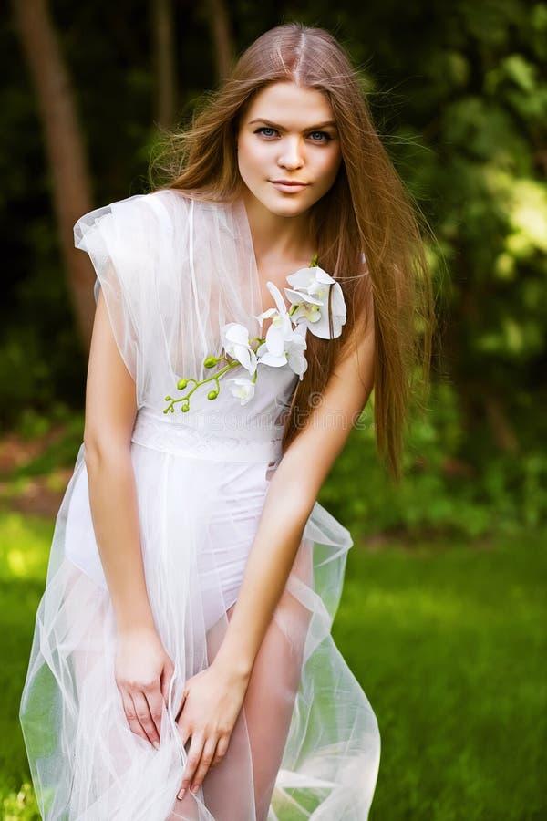 白色礼服的壮观的热的白肤金发的妇女 免版税库存照片
