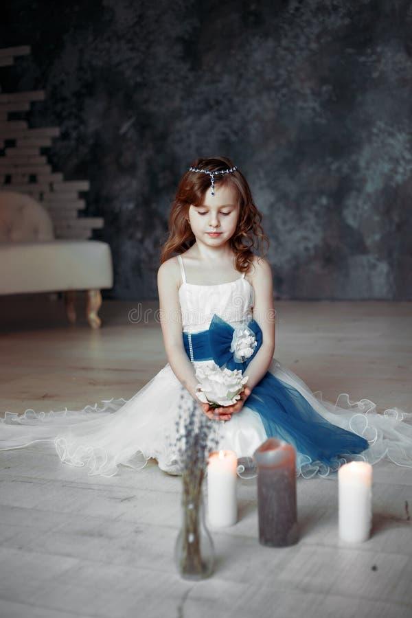 白色礼服的女孩在有蜡烛孩子的屋子里祈祷 库存图片