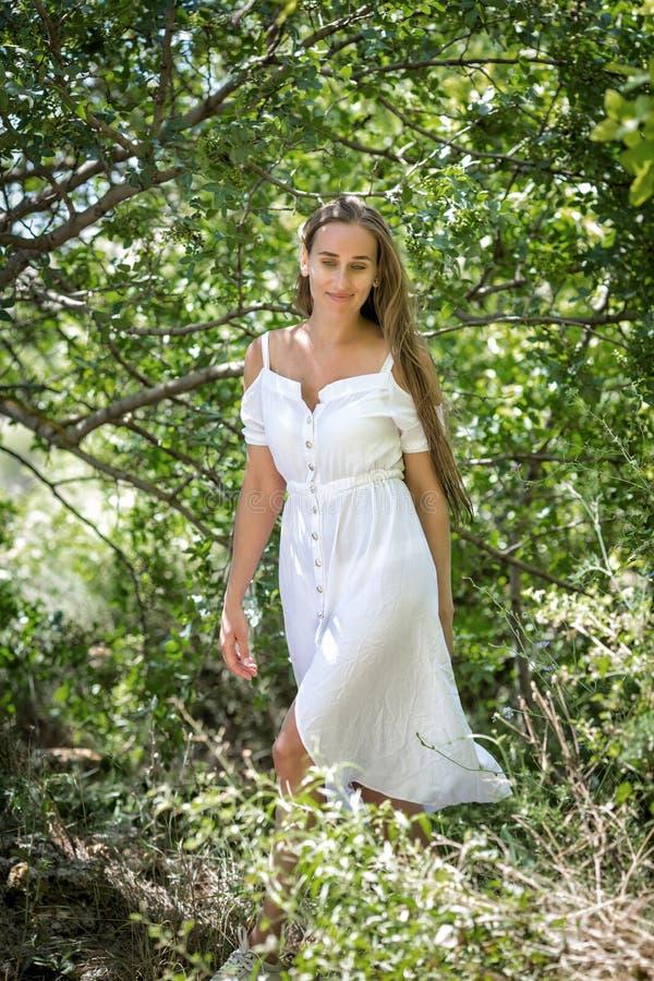白色礼服的女孩在落叶林里 图库摄影