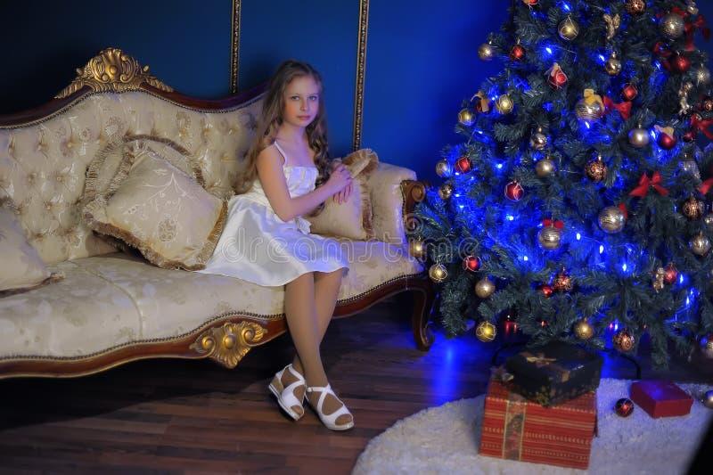 白色礼服的女孩坐沙发 免版税库存照片