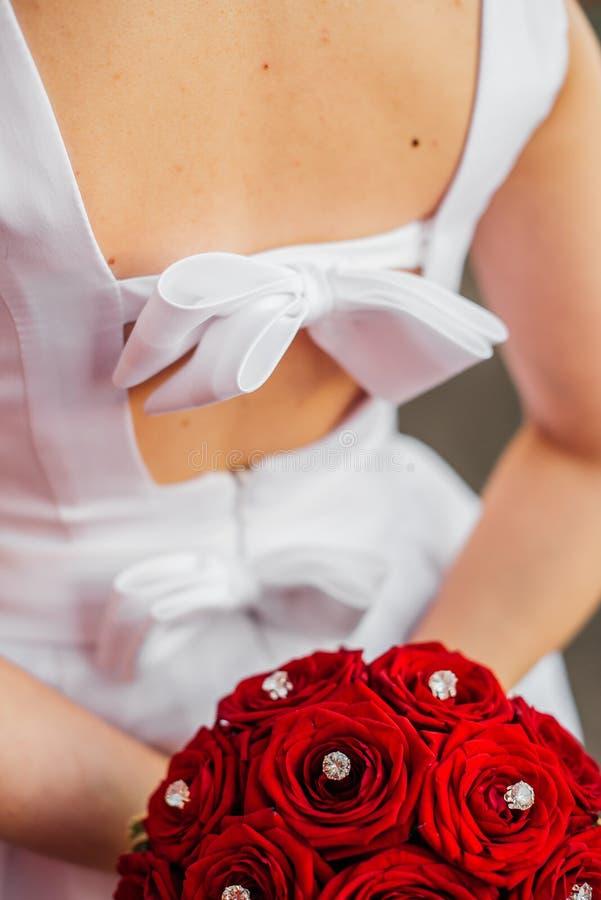 白色礼服的女孩有红色花束的 库存图片