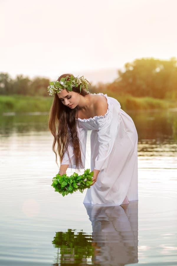 白色礼服的妇女在水中 有花圈的艺术妇女在她的头在河 缠绕在她的头,斯拉夫的传统和 库存照片