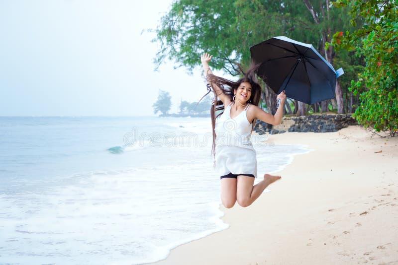 白色礼服的妇女在海滩拿着伞享用雨的 免版税库存照片