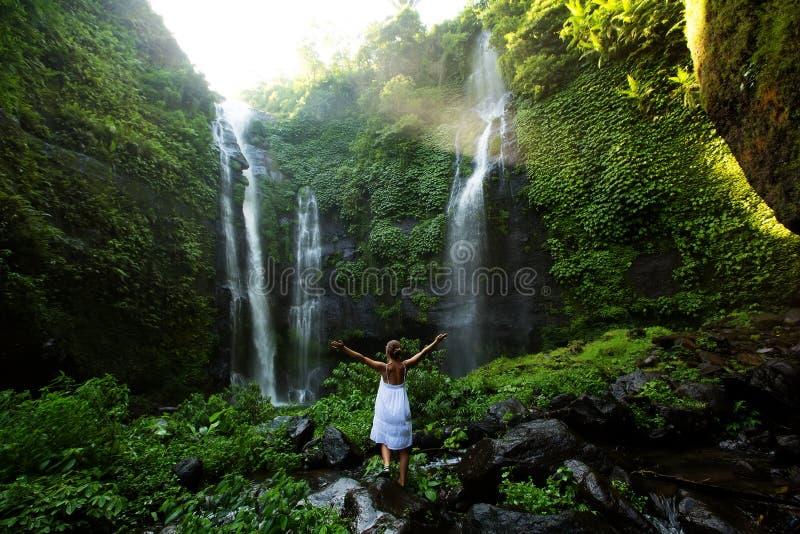 白色礼服的妇女在Sekumpul瀑布在Ba的密林 图库摄影