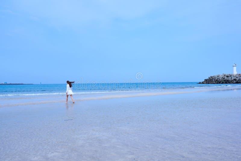 白色礼服的妇女有她吹在风的长的头发的,走在与白色灯塔的一个海滩在岩石平台在济州是 库存图片