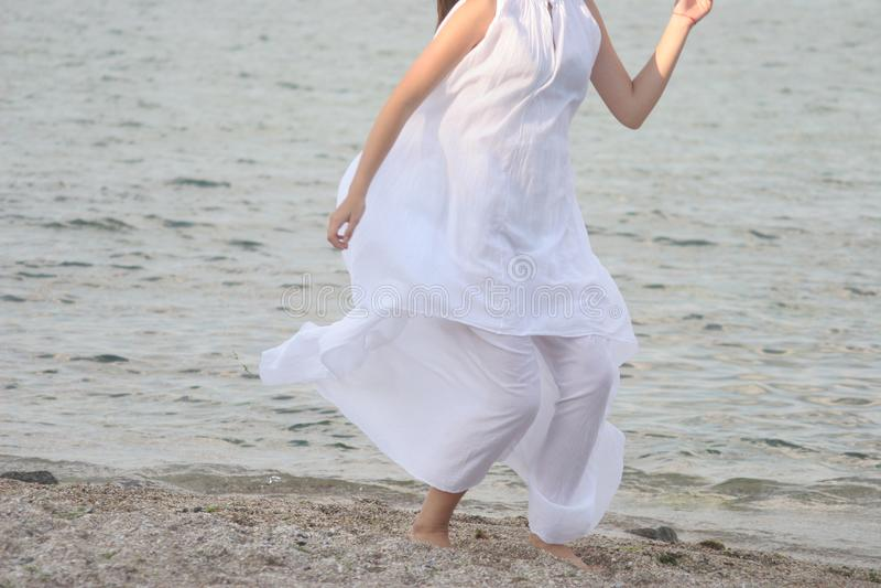 白色礼服的妇女沿沙滩跑 免版税库存照片