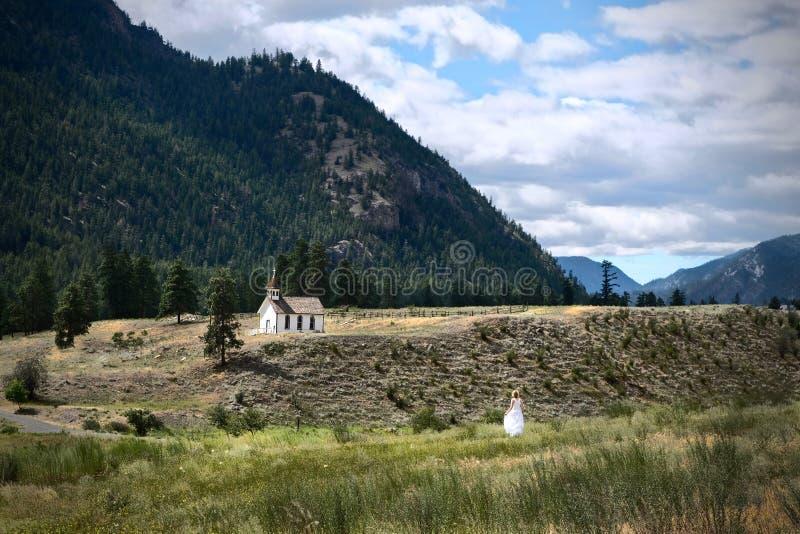 白色礼服的妇女走到教会的 免版税库存图片