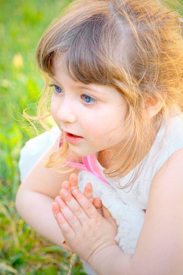 白色礼服的小白肤金发的女孩,蹲在被折叠的草坪繁忙的祈祷的手上 免版税库存图片