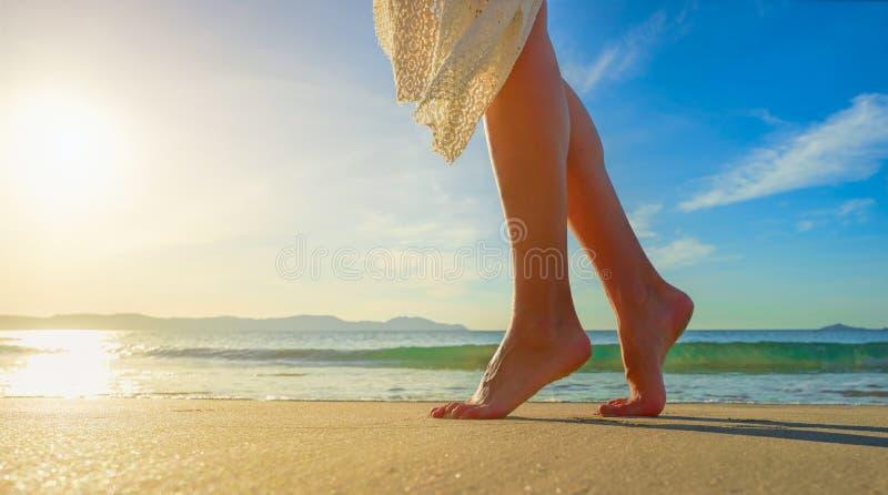 白色礼服的少妇单独走在海滩的在阳光下 库存照片