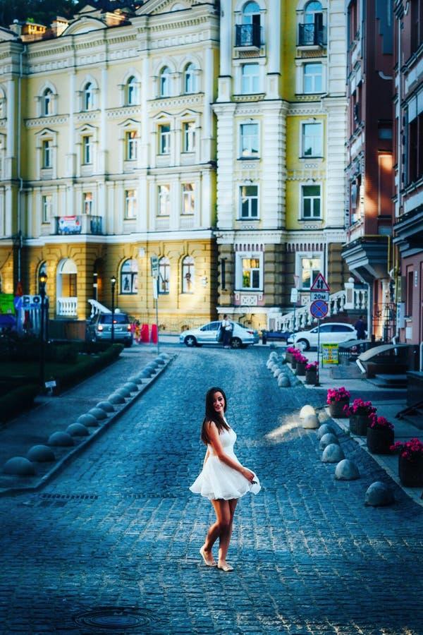白色礼服的少妇在一个空的公路交叉点的城市跳舞 活跃女孩穿有光秃的肩膀的一件白色礼服 免版税库存图片