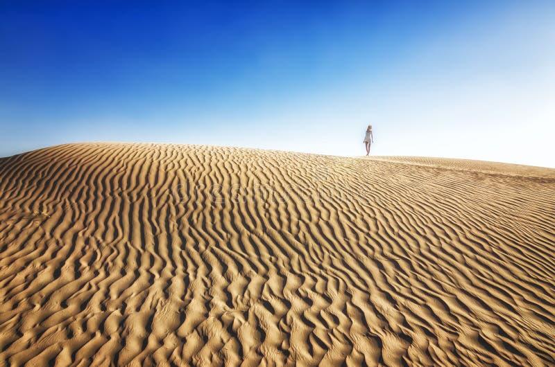 白色礼服的少妇在沙丘站立在沙漠晴朗的热的天 女孩渴 免版税图库摄影