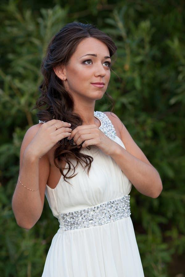 白色礼服的少妇在自然 免版税库存图片