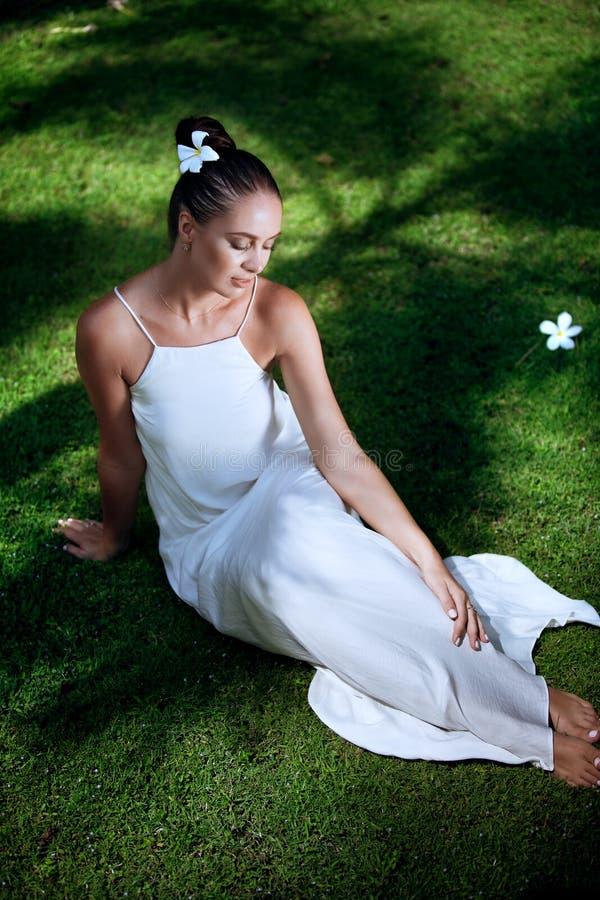 白色礼服的少妇在草 免版税库存照片