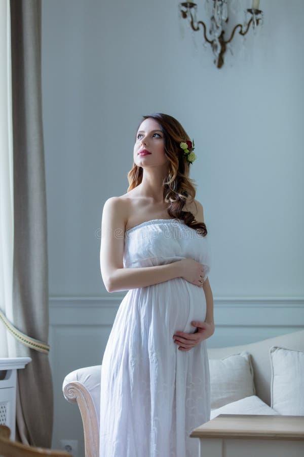 白色礼服的年轻人孕妇 免版税库存图片