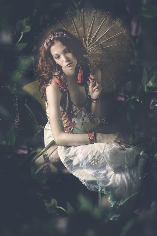 白色礼服的年轻女人有遮阳伞的在幻想庭院c里坐 免版税库存图片