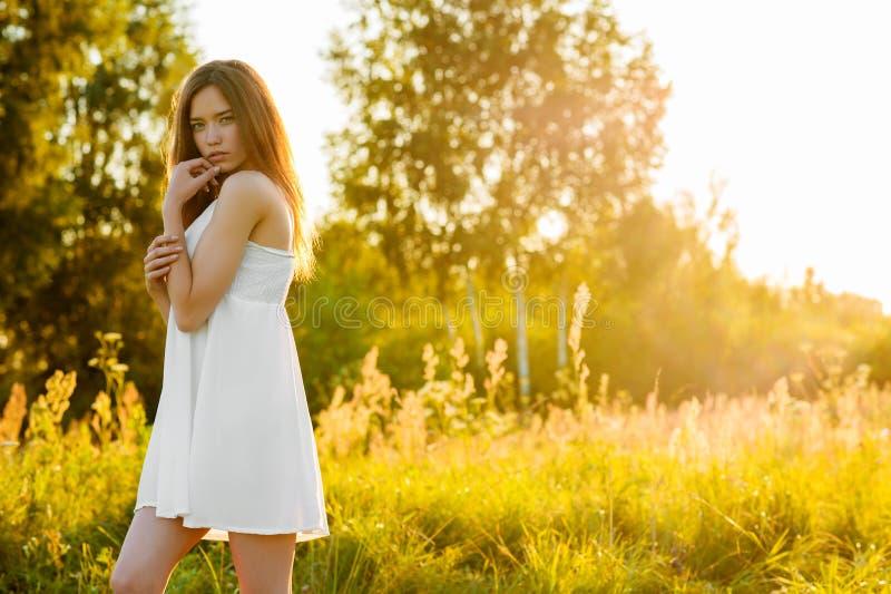 白色礼服的年轻美丽的女孩在日落 库存照片