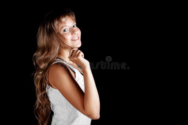 白色礼服的微笑的美丽的蓝眼睛的白肤金发的女孩在黑背景 免版税库存照片