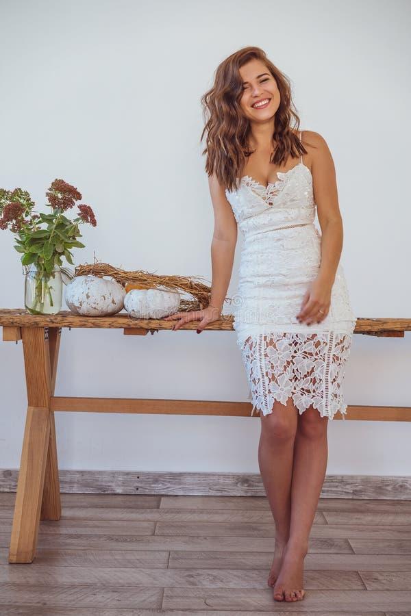 白色礼服的微笑美丽的年轻女人定调子照片 库存图片