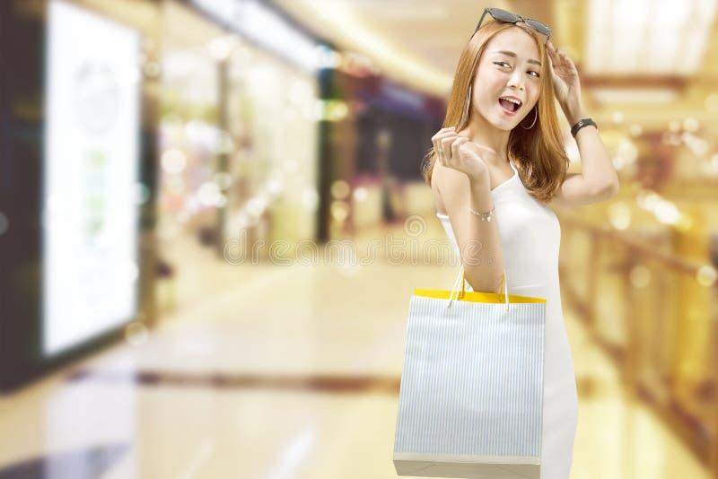 白色礼服的愉快的亚裔妇女有在购物中心的购物袋的 免版税库存图片