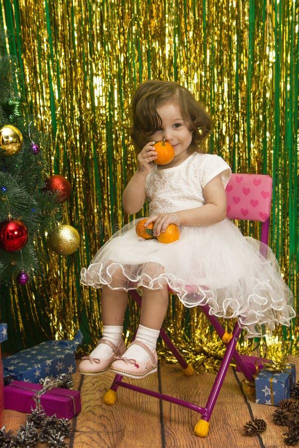 白色礼服的愉快的女孩坐椅子圣诞节backgro 库存图片