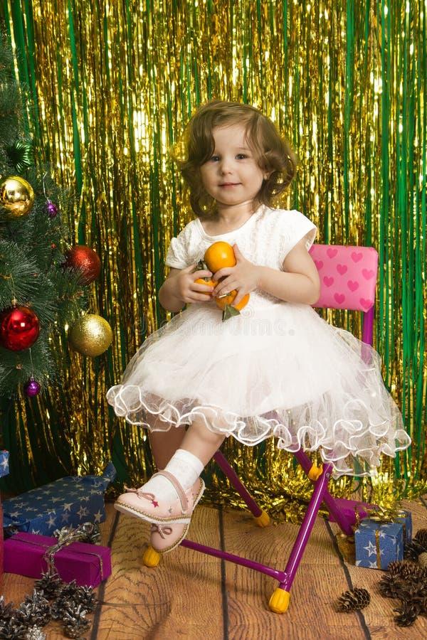 白色礼服的愉快的女孩坐椅子圣诞节backgro 免版税库存照片
