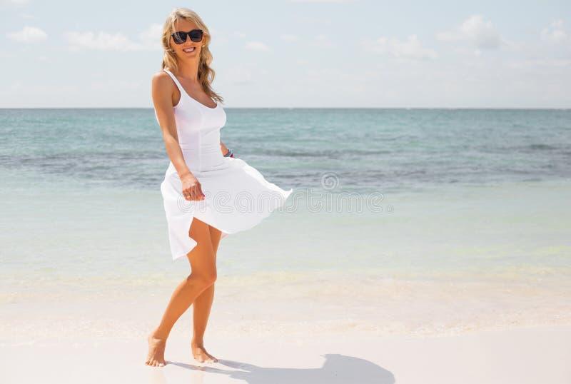 白色礼服的愉快的妇女享受在热带海滩的假期 免版税图库摄影