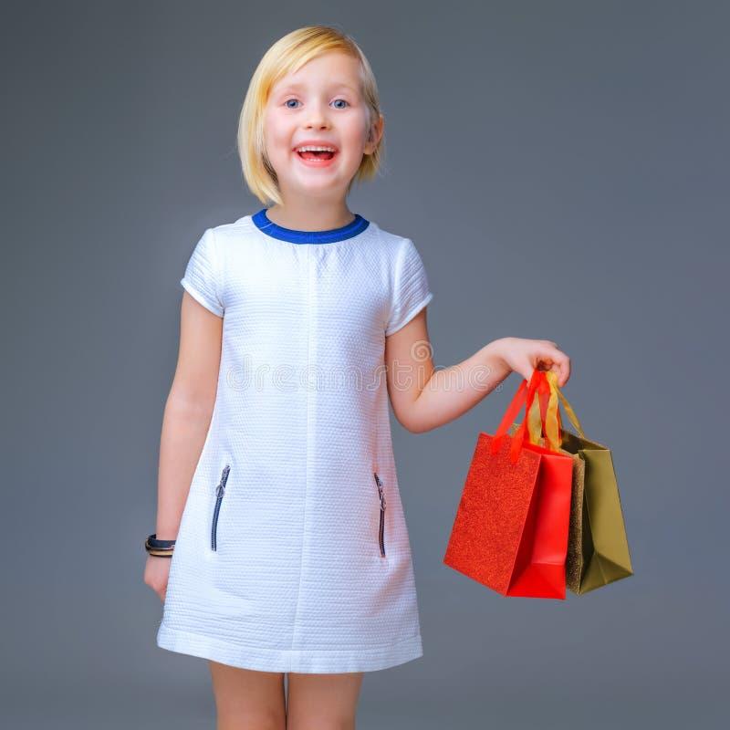 白色礼服的愉快的现代女孩在显示购物袋的灰色 免版税库存图片
