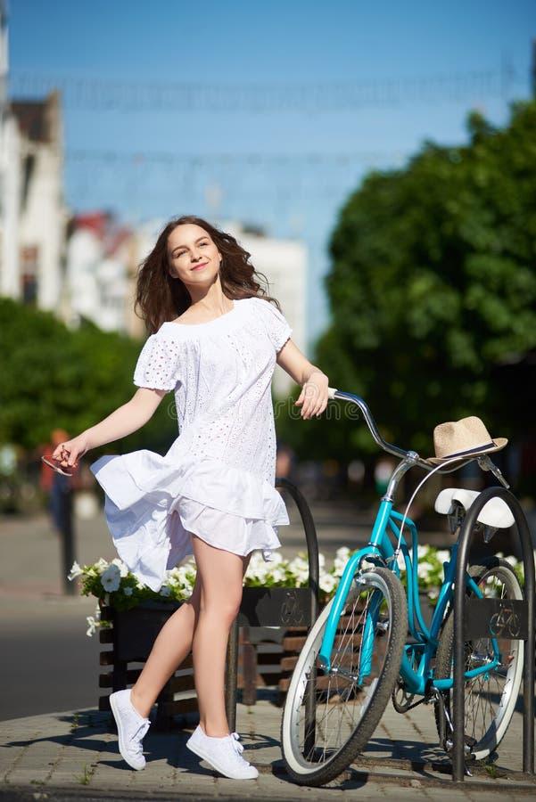 白色礼服的正面女孩享受热的夏日的站立在她的在城市街道上的蓝色自行车旁边 免版税库存照片