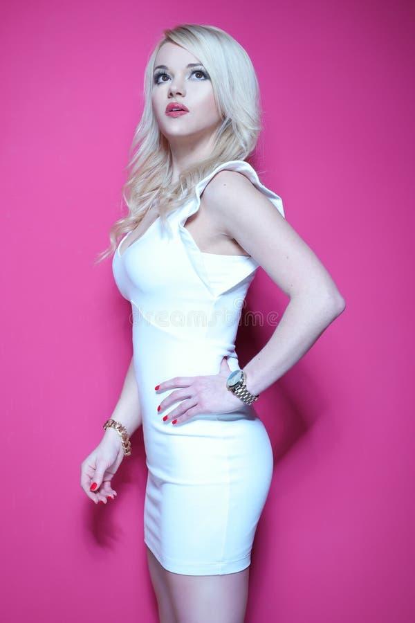 白色礼服的白肤金发的妇女在桃红色 免版税库存图片