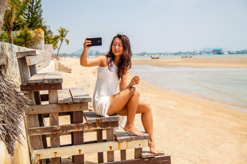 白色礼服的美丽的亚裔妇女在海滩做selfie 免版税库存图片