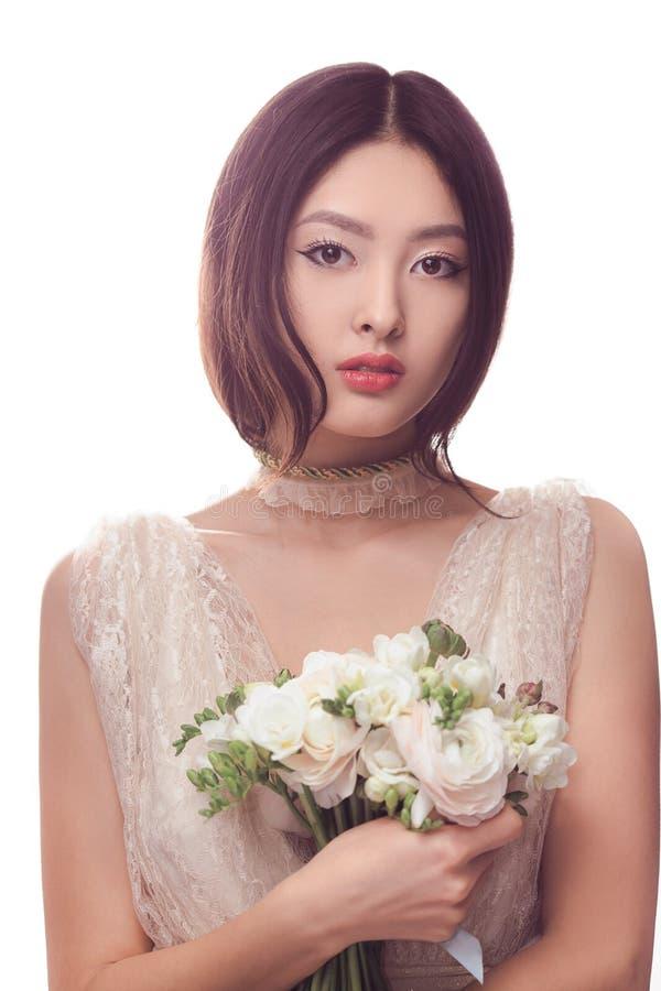 白色礼服的美丽的亚裔妇女有花花束的在手上 免版税库存照片