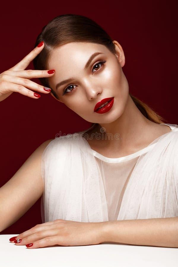 白色礼服的美丽的女孩有经典构成和红色修指甲的 秀丽表面 库存照片