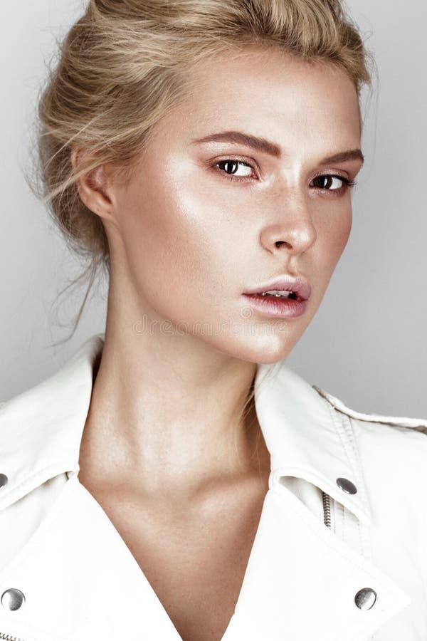 白色礼服的美丽的女孩有轻的自然构成的 秀丽表面 免版税库存图片
