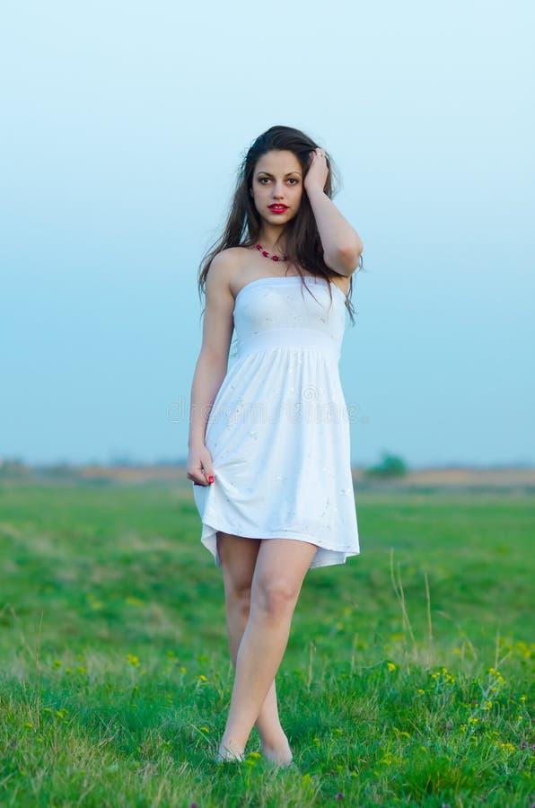白色礼服的美丽的女孩走在春天草甸的 免版税库存照片