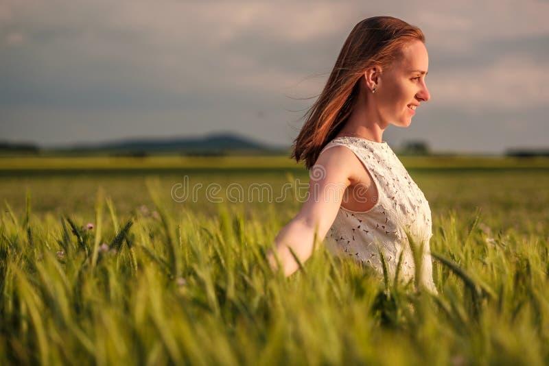 白色礼服的美丽的妇女在绿色麦田 库存图片